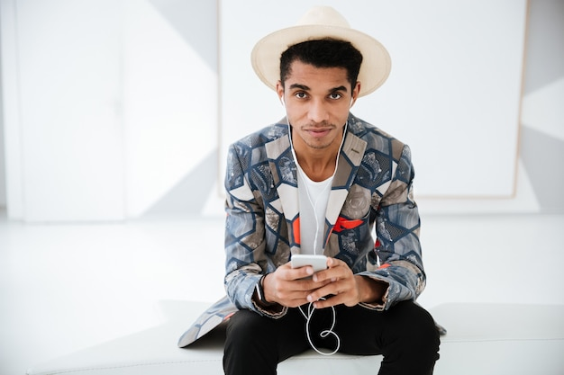 Giovane uomo d'affari africano in abito insolito e cappello ascoltando musica e seduto sul divano in ufficio.