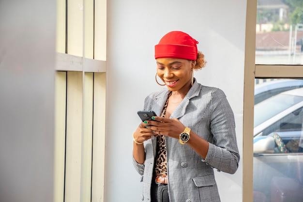 Giovane donna d'affari africana che sorride mentre usa il telefono in ufficio