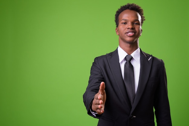 Giovane uomo d'affari africano contro il muro verde