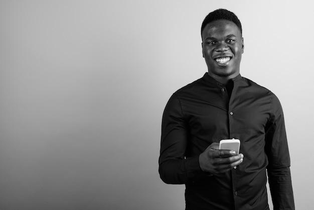 Giovane uomo d'affari africano contro il muro bianco. bianco e nero