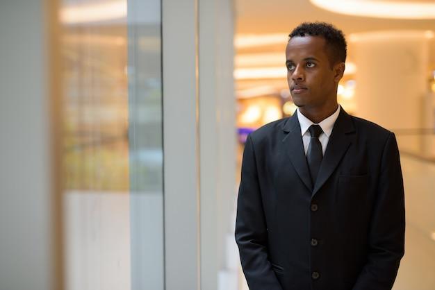 Giovane imprenditore africano guardando attraverso la finestra e pensando