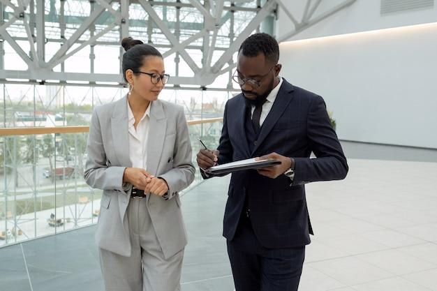 Giovane uomo d'affari africano che firma un contratto dopo aver negoziato con il partner