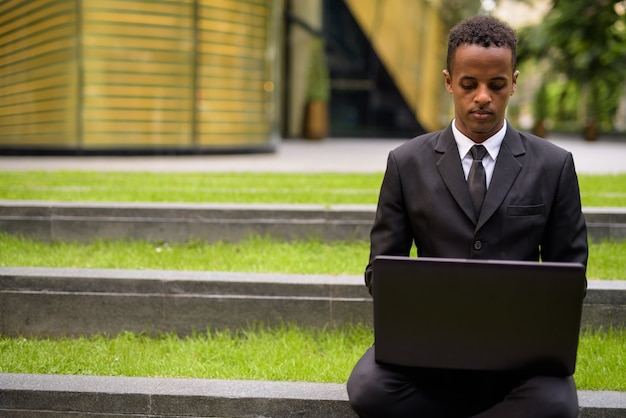 Giovane imprenditore africano seduto e utilizzando il computer portatile all'aperto