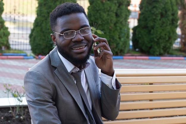 Il giovane uomo d'affari africano sorridente sulla panchina della città con telefono, tablet