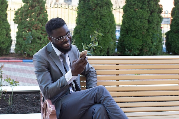 Giovane imprenditore africano sorridente sulla panchina della città con telefono, tablet