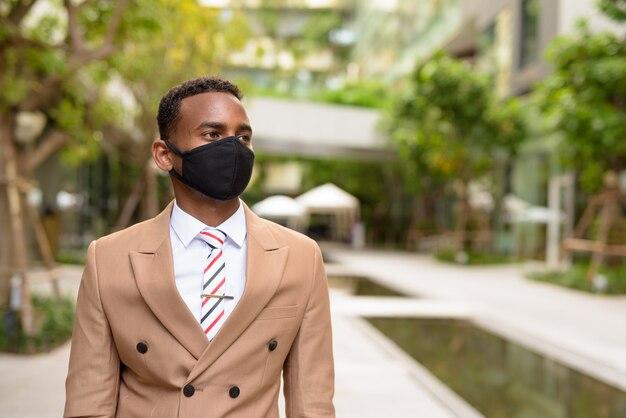 Giovane uomo d'affari africano che pensa con maschera per la protezione dall'epidemia di coronavirus in città con la natura
