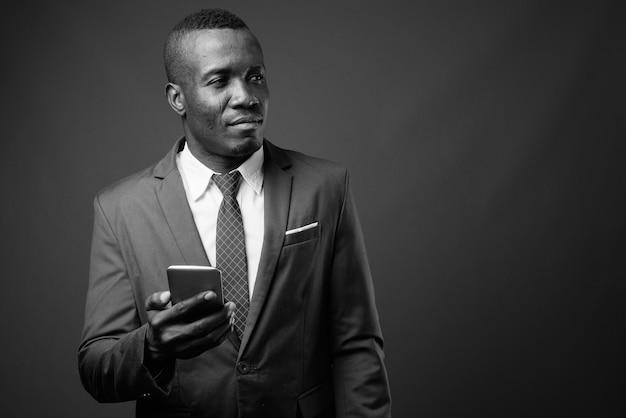 Giovane uomo d'affari africano che indossa tuta contro il muro grigio. bianco e nero