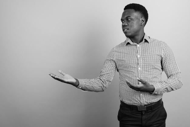 Giovane imprenditore africano con i capelli afro contro il muro bianco. bianco e nero