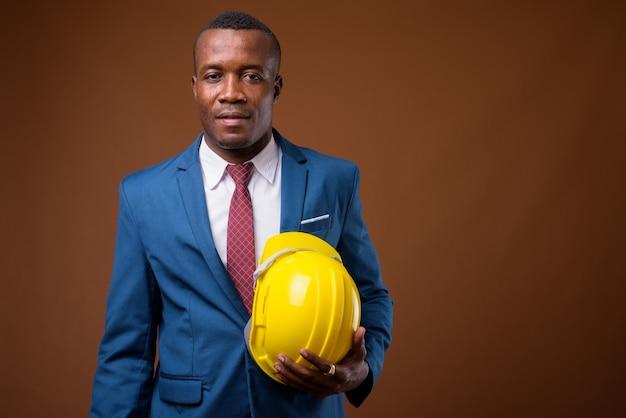 Giovane imprenditore africano con elmetto protettivo su sfondo marrone