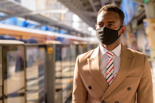 Giovane imprenditore africano con maschera pensando e in attesa presso la stazione del treno del cielo