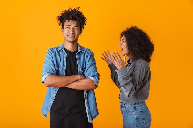 Giovane coppia africana in piedi isolato, avendo un argomento