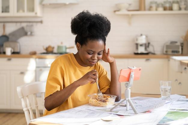 Giovane donna africana che chiama gli amici online tramite chat video nella cucina di casa durante la pausa pranzo dallo studio