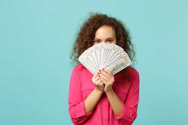 Giovane ragazza africana che copre il viso con un ventaglio di soldi in banconote in dollari, denaro contante isolato su sfondo blu turchese parete in studio. persone sincere emozioni, concetto di stile di vita. mock up copia spazio.