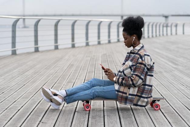 La giovane ragazza africana si siede sul longboard con lo smartphone in mano il testo all'aperto nel parco usando la connessione g