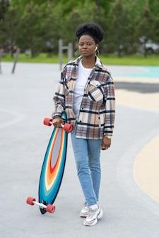 Il pattinatore della giovane ragazza africana tiene il longboard nella femmina urbana dello skate park in abiti casual nello skatepark
