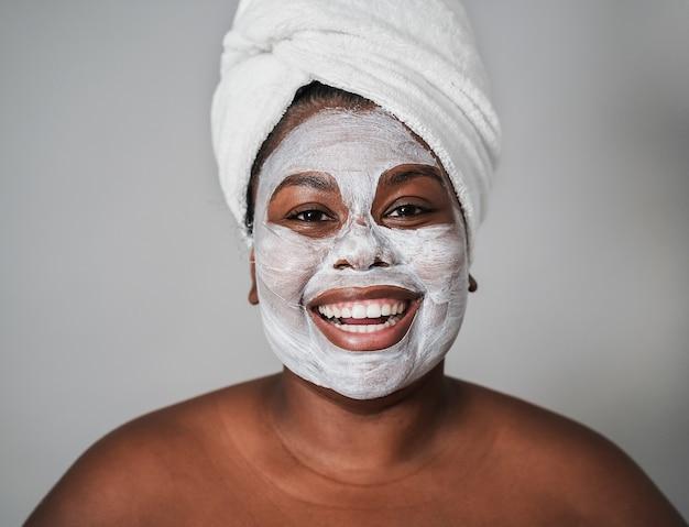 Giovane ragazza africana che indossa un trattamento con maschera per la pelle di bellezza - focus on face
