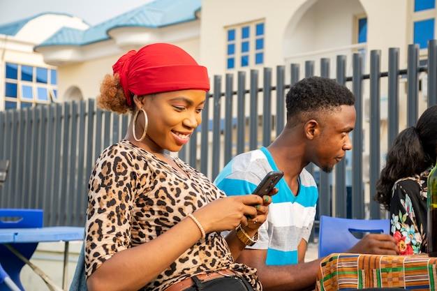Giovane signora africana che usa il suo telefono cellulare tra amici