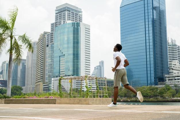 Giovane uomo africano in esecuzione all'aperto nel parco con il paesaggio urbano