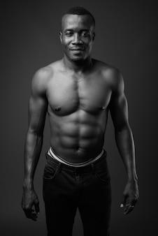 Giovane uomo africano a torso nudo contro il muro grigio. bianco e nero