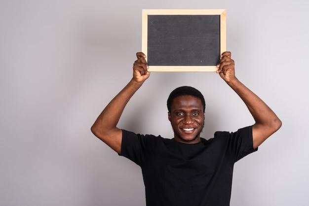 Giovane africano che indossa la camicia nera su grigio