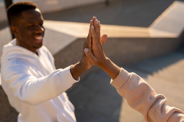 Giovane uomo africano in felpa con cappuccio bianca che dà il cinque alla ragazza caucasica mentre si saluta dopo l'allenamento in ambiente urbano
