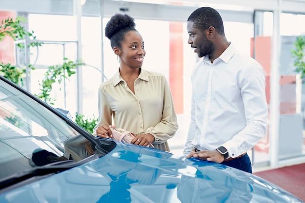 Giovane coppia di sposi africani alla ricerca della migliore auto in concessionaria