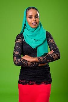 Giovane donna musulmana africana contro la chiave di crominanza con parete verde