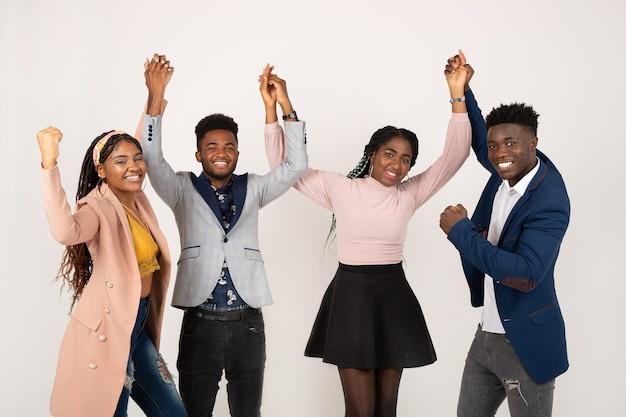 Giovani africani su sfondo bianco con le mani alzate