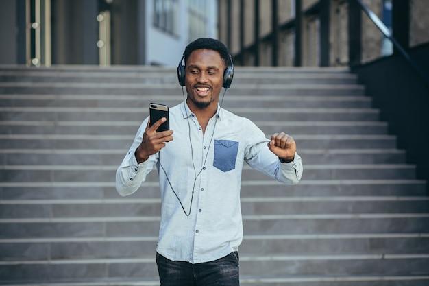 Giovane studente africano che ascolta musica dallo smartphone usando grandi cuffie, sorridendo per la comodità di usare l'app