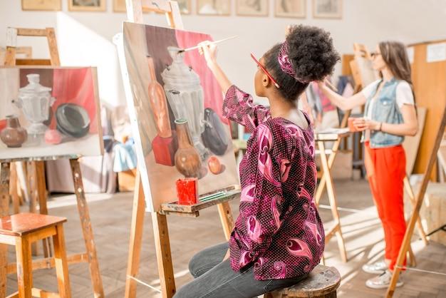 Giovane studente africano che dipinge natura morta in studio