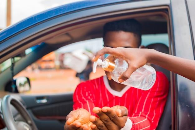 Il giovane tassista africano che indossa la maschera per il viso previene, previene, si impedisce di scoppiare nella società e usa il disinfettante per le mani per lavarsi le mani