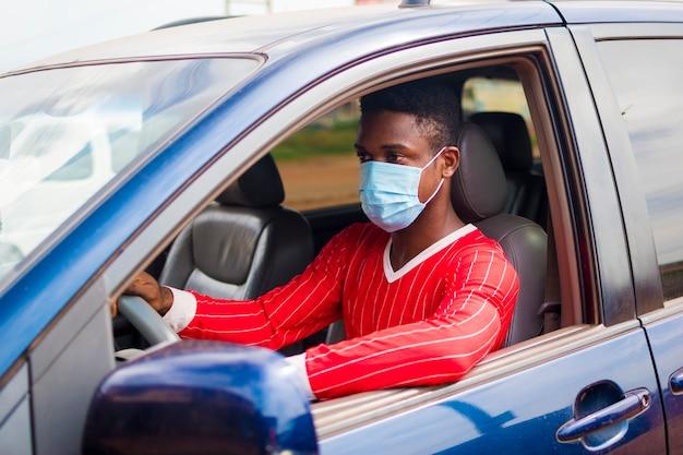 Giovane tassista africano che guida mentre usa la maschera facciale per prevenire, prevenire, prevenire l'epidemia nella società