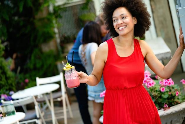 La giovane donna africana si gode un sano frullato vegetariano per la perdita di peso e la disintossicazione