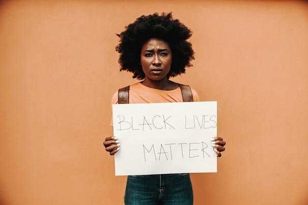 Carta della tenuta della giovane donna africana con il titolo black lives matter.