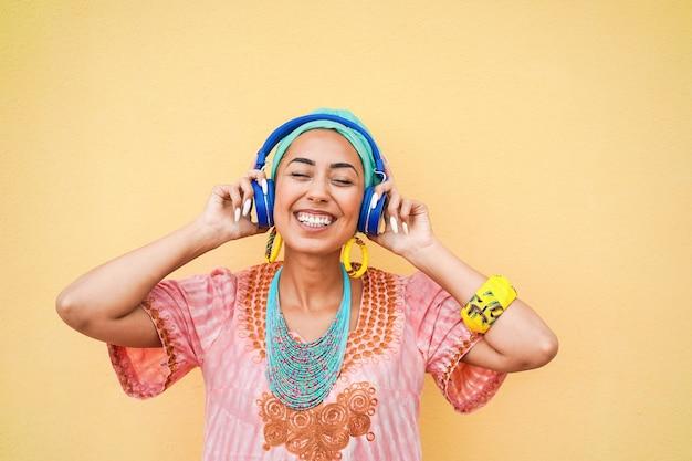 Musica d'ascolto della giovane donna africana con le cuffie - focus sul viso