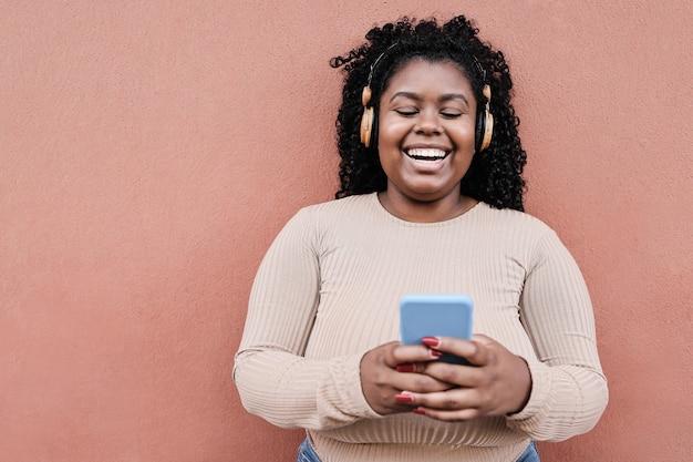 Giovane donna africana ascoltando musica con le cuffie all'aperto in città - focus sul viso