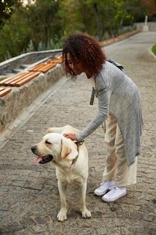 Giovane donna africana che petting un cane sulla strada