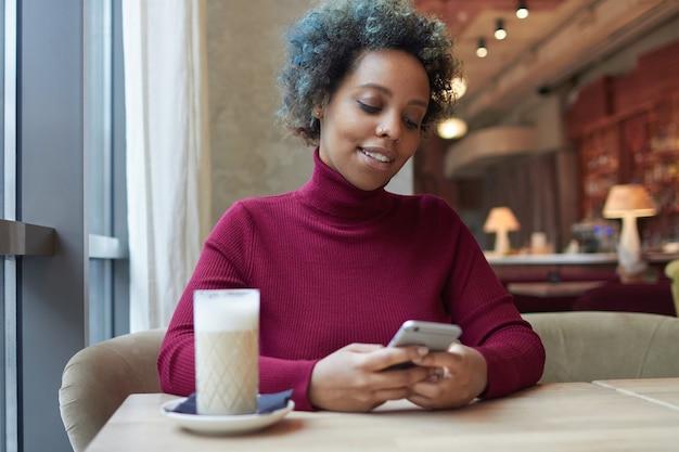 Giovane donna africana che naviga in internet o usa l'app di appuntamenti con il suo telefono in un accogliente caffè