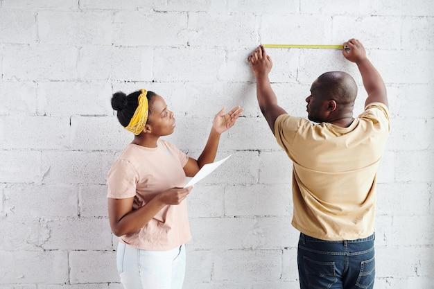 Giovane donna africana con carta in piedi accanto a suo marito che misura la lunghezza dei mattoni del muro e si consulta con lui durante la ristrutturazione della casa