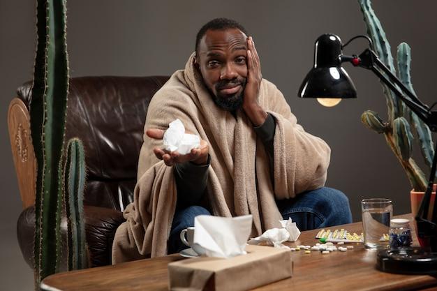 Il giovane afroamericano avvolto in un plaid sembra malato e ha un terribile mal di testa seduto a casa