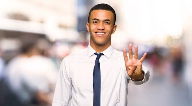 Giovane uomo d'affari afro americano felice e contando quattro con le dita nella città