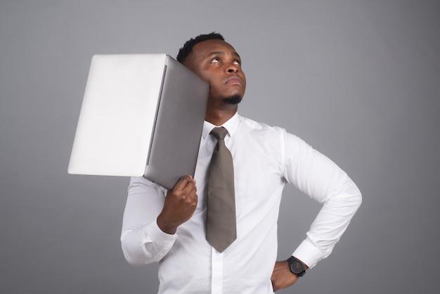 Giovane uomo d'affari afroamericano che utilizza laptop e prende appunti.
