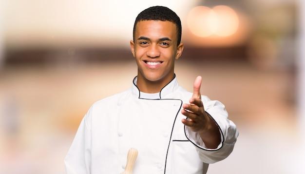 Giovane uomo afro american chef stringe la mano