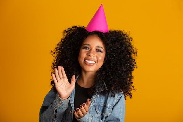 Cappello da portare di compleanno della giovane donna afroamericana sopra la parete gialla isolata con un sorriso felice e freddo sul fronte. persona fortunata.