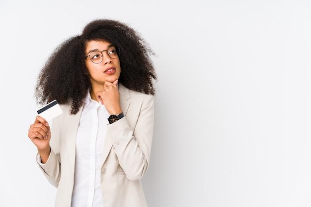 Giovane donna afro di affari che giudica un'automobile di credito isolata. giovane donna di affari afro che tiene un'automobile di credito che guarda lateralmente con l'espressione dubbiosa e scettica.