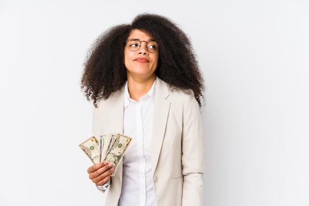 Giovane donna d'affari afro in possesso di un credito auto isolata giovane donna d'affari afro in possesso di un credito inconfondibile, si sente dubbioso e incerto.