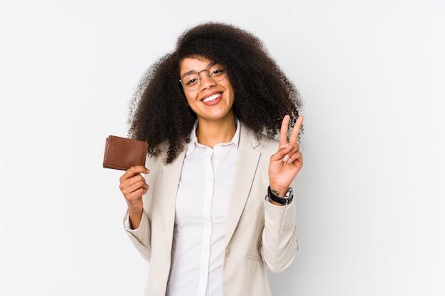 Giovane donna d'affari afro in possesso di una macchina di credito isolata giovane donna d'affari afro in possesso di un numero due auto di credito con le dita.