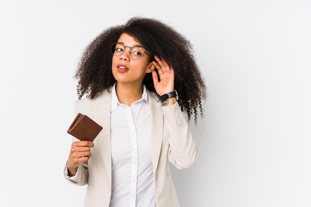 Giovane donna d'affari afro in possesso di una macchina di credito isolata giovane donna d'affari afro in possesso di un credito cartrying ad ascoltare un pettegolezzo.