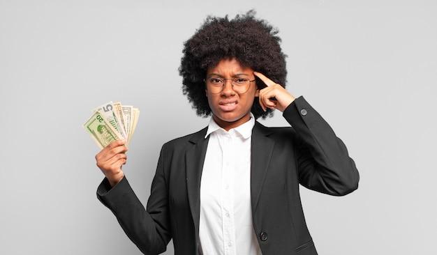 Giovane imprenditrice afro sentirsi confusa e perplessa, dimostrando che sei pazzo, pazzo o fuori di testa. concetto di affari