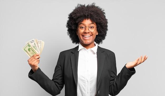 Giovane imprenditrice afro sentirsi felice, sorpresa e allegra, sorridente con atteggiamento positivo, realizzando una soluzione o un'idea.